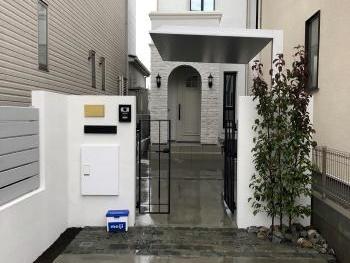 白い門柱とブラック門扉にグレーのブロック。下からあたる照明がお気に入りです。